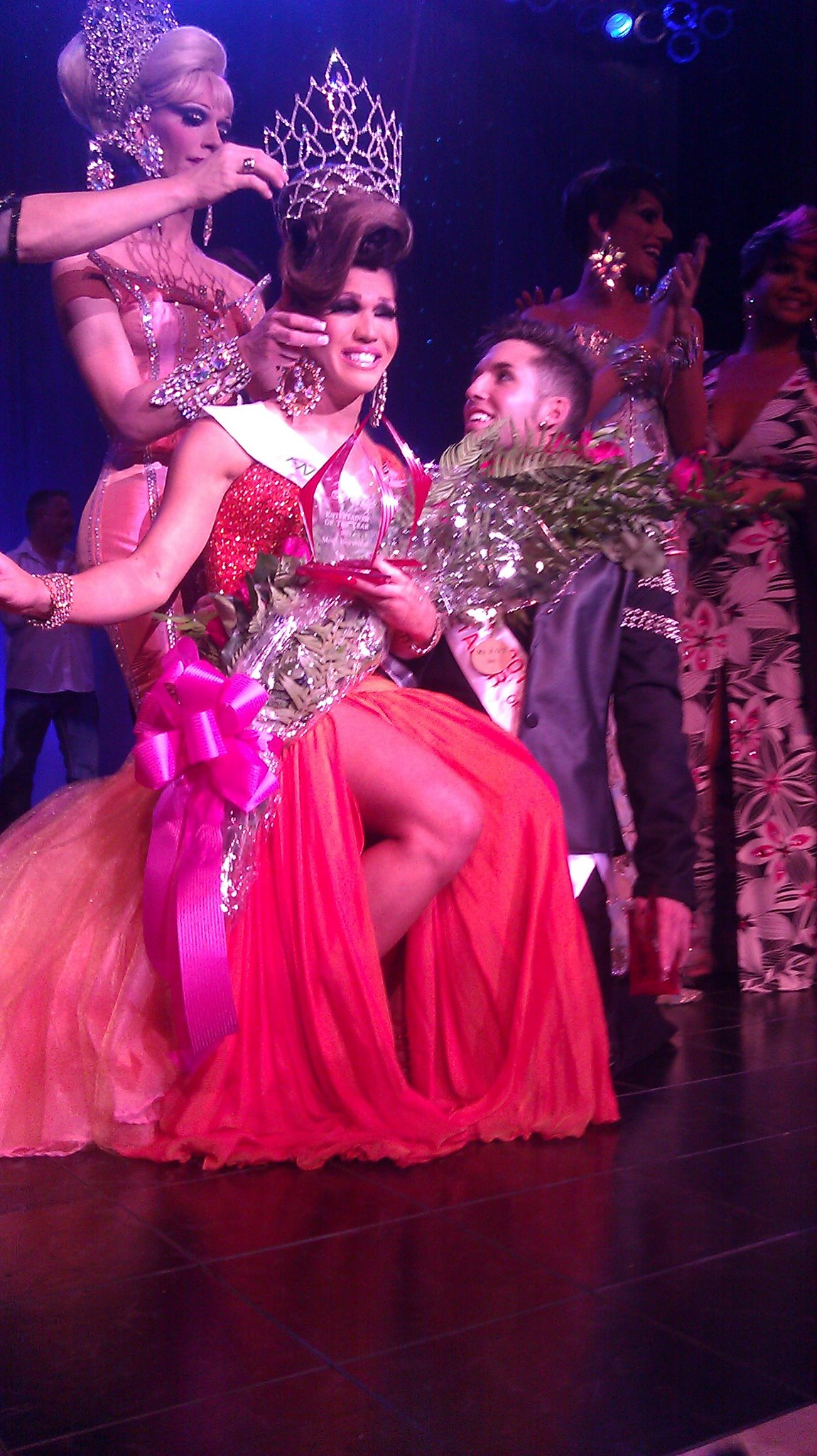 Aurora Sexton, on the knee of Mykul Jay Valentine, being crowned National Entertainer of the Year, F.I. 2011 by the outgoing Vanessa DeMornay.